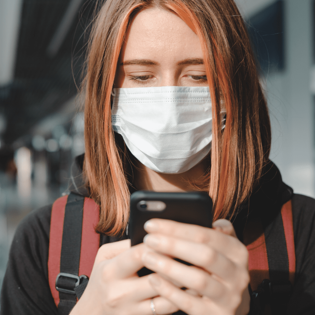 Woman with facemask holding smartphone.